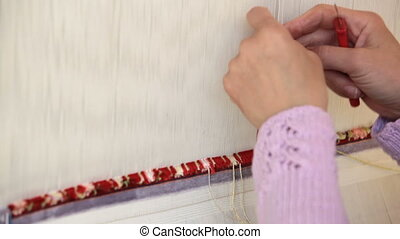Woman weaving a carpet by hand