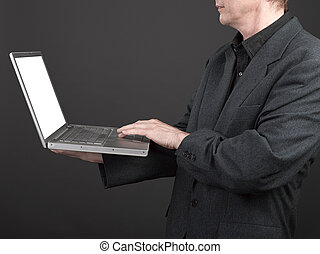 Man in black shirt and suit holding a laptop for working on...