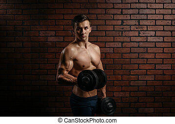 Young sports guy trains biceps