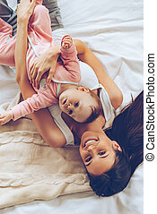 Morning hugs. Top view of cheerful beautiful young woman looking at camera with smile and hugging her baby girl while lying in bed