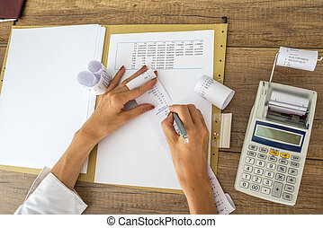 Female accountant or tax adviser working with receipts and...