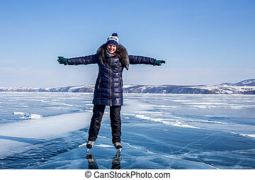 Happy young woman skating on the frozen Lake Baikal