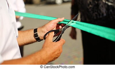 man cuts the Ribbon with scissors