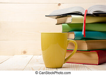 Stack of colorful books, open book and cup on wooden table....
