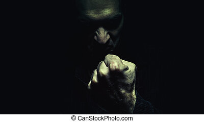 Evil Man With the Fist - Dark person showing the fist. Man...