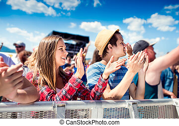 Teenagers at summer music festival clapping and singing