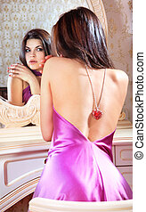 lady looks in a mirror - beautiful young lady at mirror...