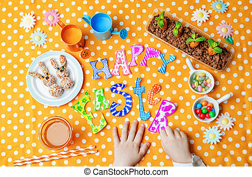 Happy Easter words with childrens hands and sweets and juice...