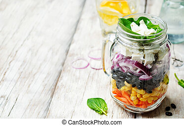 Carrot corn black beans red onion feta spinach salad in a...