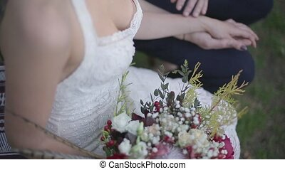 Bride sitting with flowers and holding the hand of the...