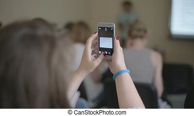 Girl makes a photo on smartphone during the conference.