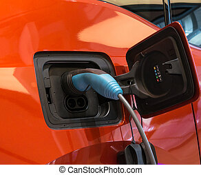 Charging an electric car with the power cable supply plugged...