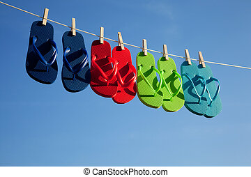 Row of flipflops against a blue sky - Blue, green, red,...