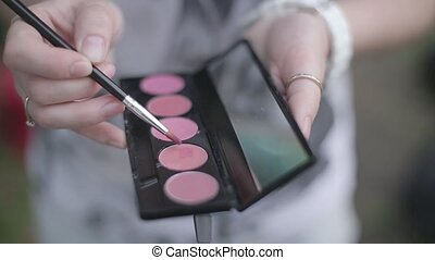 Girl holding a brush and cosmetics for make-up