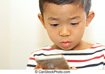 Japanese boy using a smart phone (6 years old)