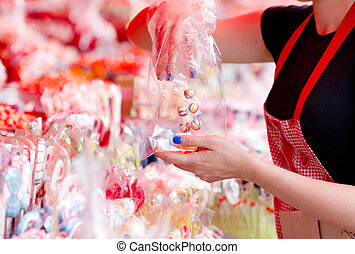 Confectionery - Young woman putting colorful candies in a...