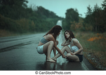 Women quarrel in rain on the road - A couple of young girls...