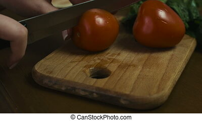 Woman cuts a whole tomato to two big slices on a wooden...