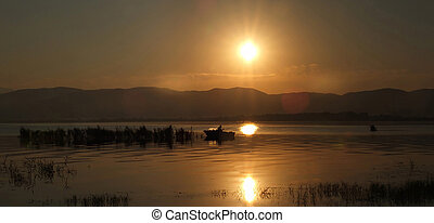 Sunrise over Dojran Lake and fisherman between reeds -...
