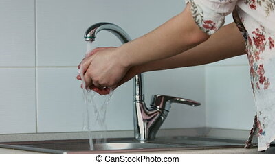 Picture of a woman opens a tap and washes a tomato in a...