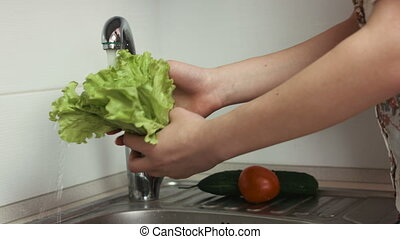 Woman washes lettuce leaves and other vegetables in the kitchen before cooking.