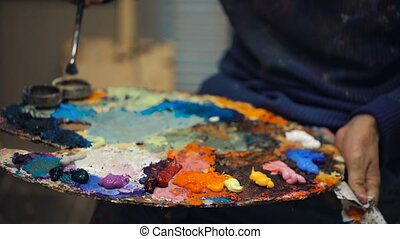 artist brush mix color oil painting on palette is holding in...