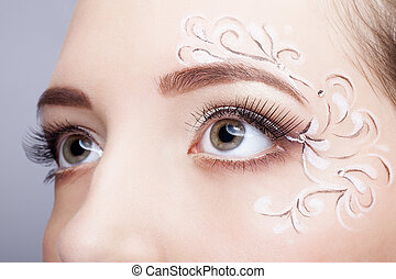 Close-up portrait of young woman with face art make up -...