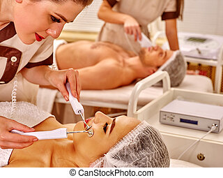 Young woman receiving electric facial massage - Young family...