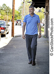 Man Walking - A Man Walking down a sidewalk next to...