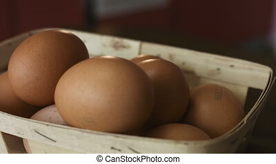 Close-up footage of basket of brown eggs lie on a wooden...