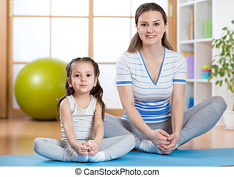 Happy mom and kid daughter spends time in the gym