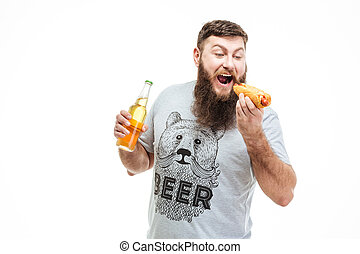 Bearded man holding bottle of beer and eating hot dog -...