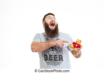 Happy bearded man holding small teddy bear and laughing