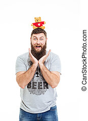 Cheerful funny man with beard put teddy bear on head -...