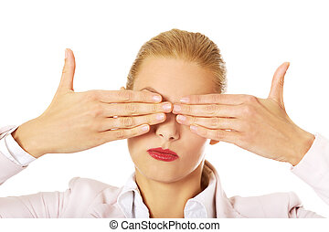 Business woman covering her eyes with her hands See no evil...