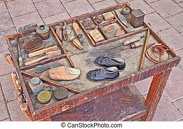 old tools of the shoemaker - work table with small shoes for...