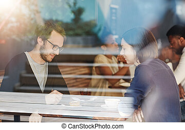 Couple on a coffee date at busy modern cafe