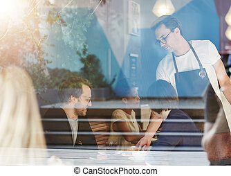 Couple being served by a waiter in busy cafe