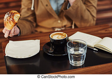 Table with coffee, notebook and person eating a croissant -...