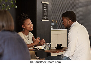 African couple enjoying coffee date in a modern cafe -...