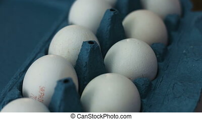 Dozen of white eggs lie in a blue carton box and spinning...