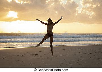 Ballet dancer on beach at sunrise.