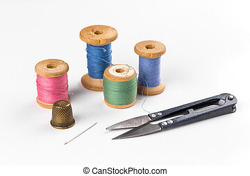 Colored thread with scissors on white background