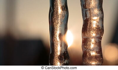 Two icicles in the evening against the sun Video full hd