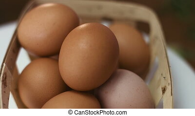 Close-up footage of a dozen of brown eggs in a wooden basket spinning around.