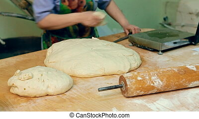 A baker is cutting dough - The cook is cutting off a portion...