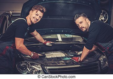 Professional car mechanics checking under hood in auto...