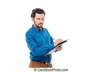 Businessman writing notes in clipboard
