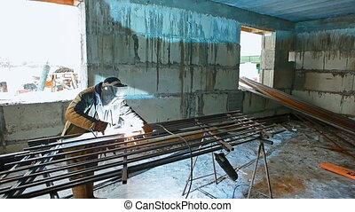 A welder is welding in winter - A welder in mask is welding...