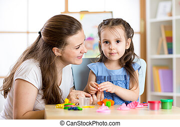 Mother and child daughter at home molded from clay and play together. Concept of preschool or home education.